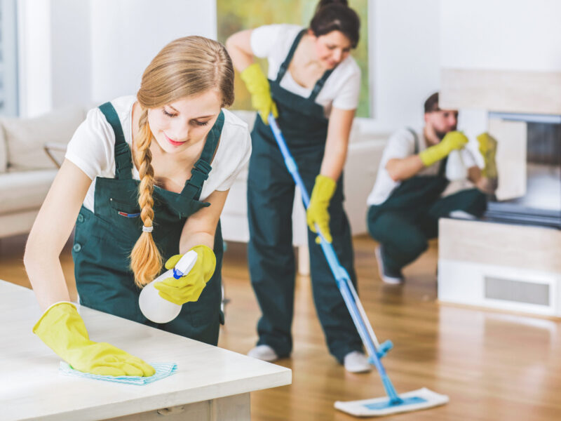 Young member of a cleaning crew wearing green overalls and yellow gloves wiping a white table in apartment interior with the rest of the team in blurred background